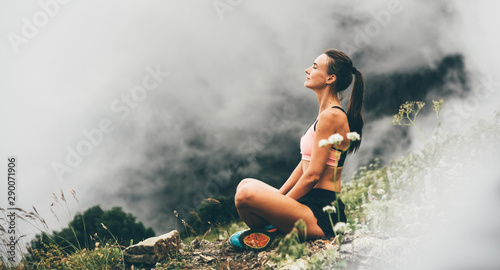 Obraz Woman meditating on mountain cliff above the clouds. Alone travel healthy lifestyle. Healthy life Concept. - fototapety do salonu