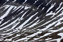 Snow Parches On Barren Arctic Mountain
