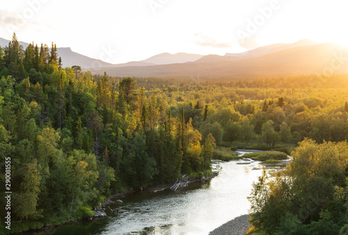 Wall mural - The sun setting over a river in a   mountain wilderness.  Jamtland, Sweden.