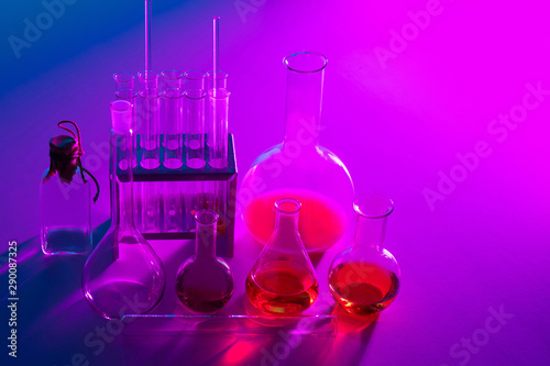 Glass flasks. Concept the science of chemistry. Chemical lab. Flasks with multi-colored liquids.Chemistry.Flasks on a pink background. Chemical beakers.Laboratory glassware. Laboratory diagnostics.