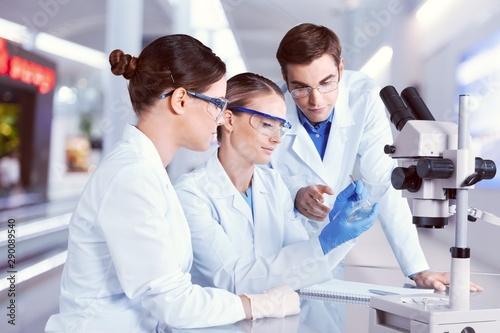 Slika na platnu Female and male scientists in glasses working with microscope
