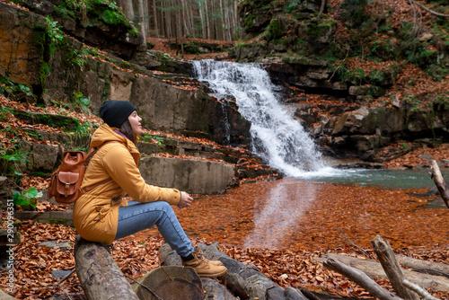 Foto auf Leinwand Dunkelbraun woman sitting on the log looking at waterfall autumn season