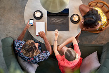 Candid Overhead Shot Of Three Multi-ethnic Millennial Coworkers Collaborating Over Coffee With Laptop Computer At Bright Cafe Serving Fair-trade Coffee