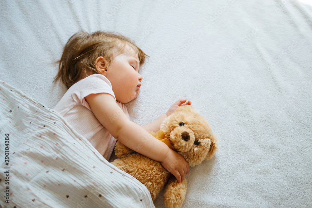 Fototapeta Little baby sleeping on bed embracing soft toy, free space