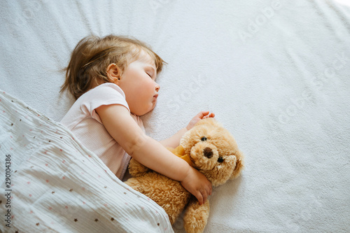 Photo  Little baby sleeping on bed embracing soft toy, free space