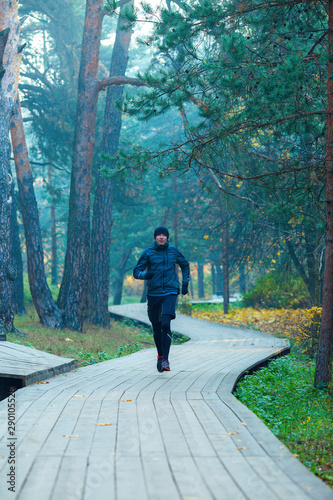 Image of running athlete in autumn park.