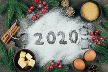 Christmas Or New Year Concept. 2020 Text Made With Flour With Bakery Ingredients And Festive Christmas Decoration On Table.