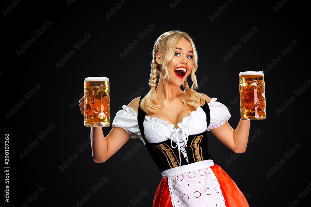 Fototapeta Happy sexy oktoberfest girl waitress, wearing a traditional Bavarian or german dirndl, serving two big beer mugs with drink isolated on black background.