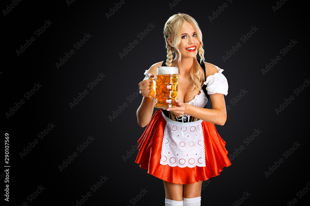 Fototapety, obrazy: Smiling young sexy oktoberfest girl waitress, wearing a traditional Bavarian or german dirndl, serving big beer mug with drink isolated on black background.