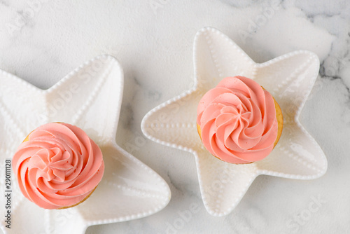 two pink cupcakes on star plates Wallpaper Mural