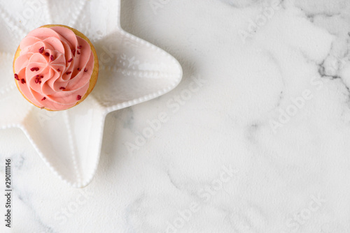 Photo  Pink cupcake on star plate. Copy space