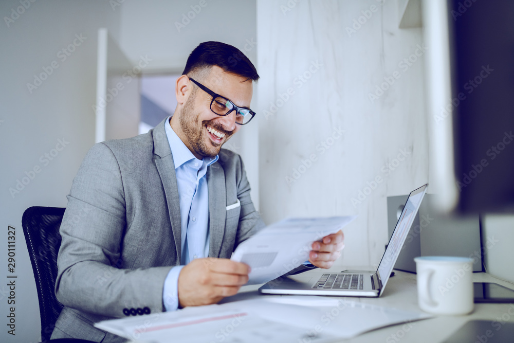Fototapety, obrazy: Smiling hardworking caucasian manager in gray suit sitting in modern office and reading report. On desk are laptop and mug with coffee.