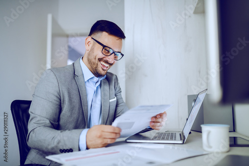 Smiling hardworking caucasian manager in gray suit sitting in modern office and reading report. On desk are laptop and mug with coffee.