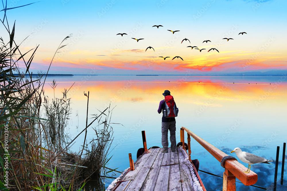 Fototapeta hombre aventurero en el embarcadero del lago