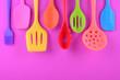 Leinwanddruck Bild - bright multi colored kitchen utensils on purple background with copy space