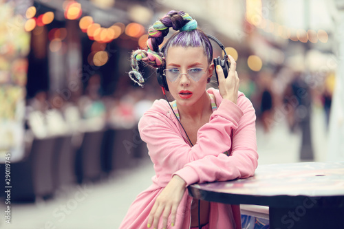 Young woman listening to music via headphones on the street - Hipster Girl with a nonconformist fashion look - 290119745