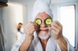 Leinwanddruck Bild - Senior man with cucumber on front of his eyes in bathroom indoors at home.