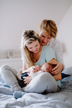 Beautiful Young Parents With A Newborn Baby At Home, Sitting On Bed.