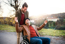 Young Man And His Senior Father In Wheelchair On A Walk In Town.