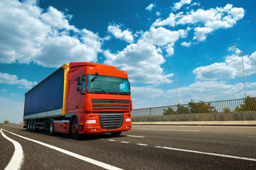 Red truck is on highway - business, commercial, cargo transportation concept