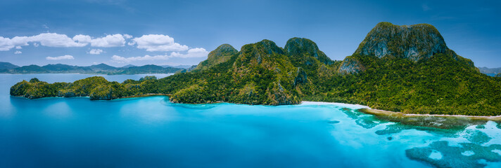 Aerial drone panoramic view of uninhabited tropical island with rugged mountains, rainforest jungle, sandy beaches surrounded by blue ocean