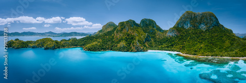 Printed kitchen splashbacks Island Aerial drone panoramic view of uninhabited tropical island with rugged mountains, rainforest jungle, sandy beaches surrounded by blue ocean