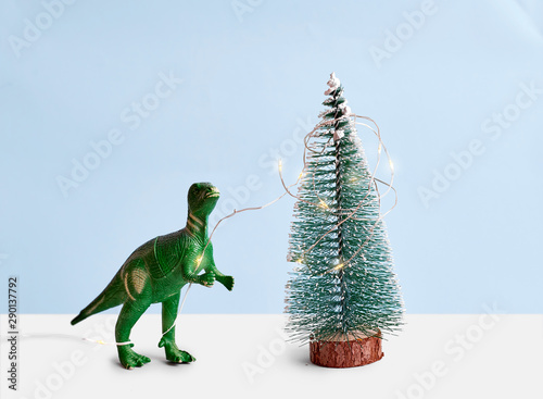 Fotografie, Obraz  Funny green Tyrannosaur Rex with lights decorating pine tree