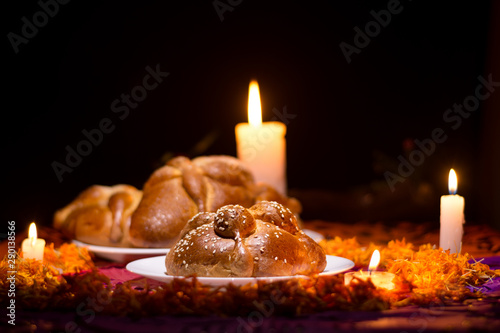 Pan de Muerto traditional recipe from Mexico, adorned with candles and cempasuchil flower petals, in the diffuse background, commemorating the Day of the Dead Fototapete