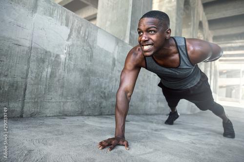 Fotografía  Intense push ups muscular male athlete training in city urban location, downtown