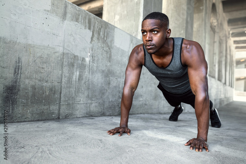 fototapeta na drzwi i meble African american male athlete, city urban training, fitness push ups on concrete with copy space