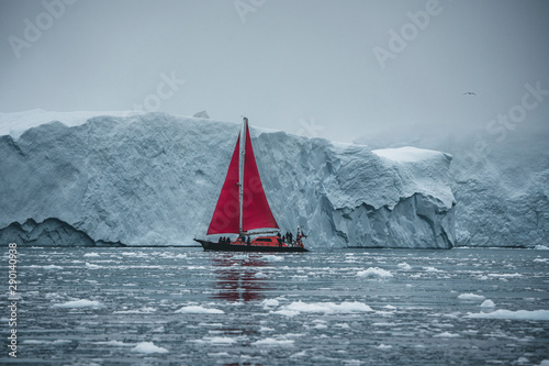 Fototapeta  Beautiful red sailboat in the arctic next to a massive iceberg showing the scale