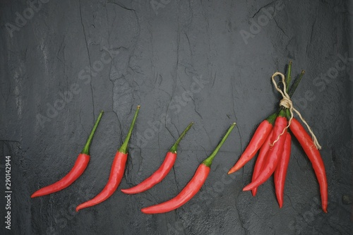 La pose en embrasure Hot chili Peppers Flat lay of red chili peppers on vintage black slate stone surface with copy space
