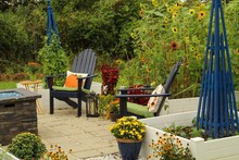 Outdoor Patio Decorated For Autumn With Pumpkins, Pillows, Plants And Hay Bales, Lanterns