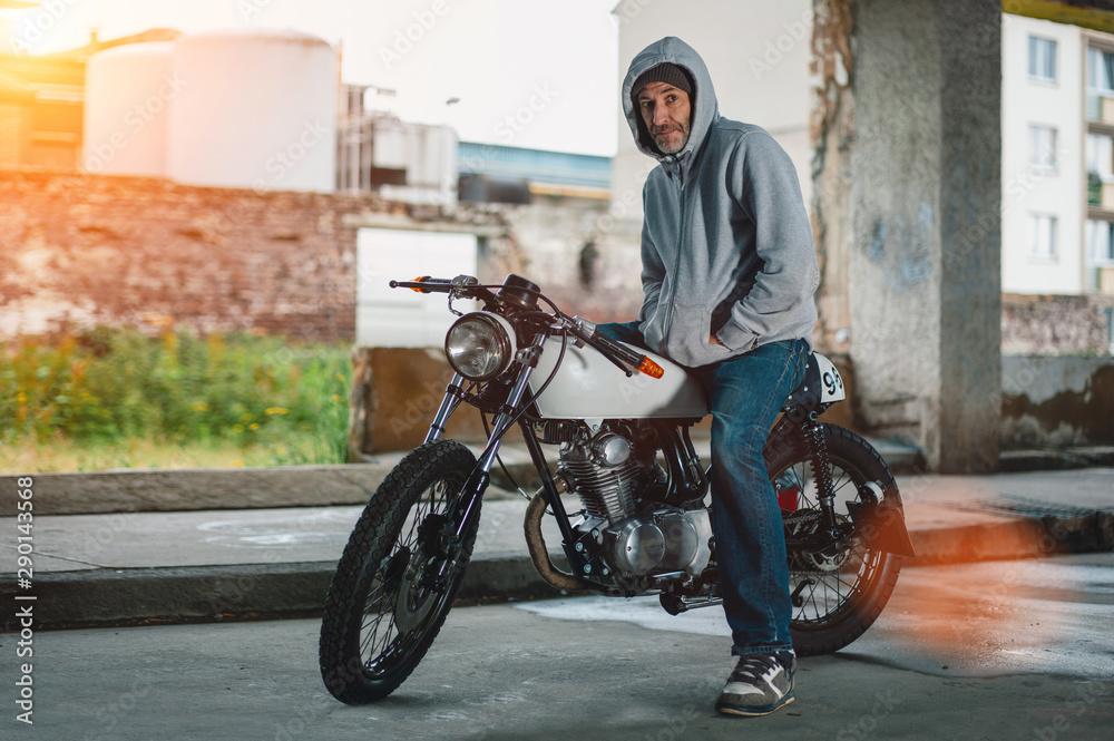 Fototapeta man on his vintage retro motorcycle looking into camera