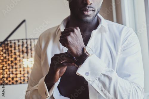 Fotografía Sexy confident male in opened white shirt is putting on his wrist watch