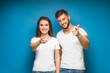 canvas print picture - Pretty, young happy couple love smiling point finger to empty copy space, man and woman smile looking up, isolated over background