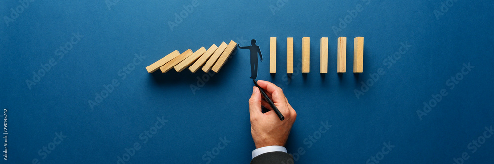 Fototapeta Silhouette of a man making a stop gesture to prevent wooden dominos from collapsing
