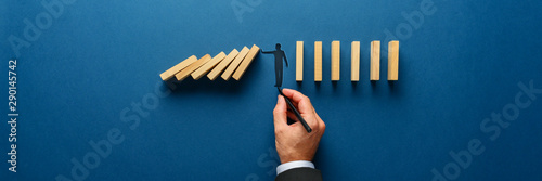 Fotografía  Silhouette of a man making a stop gesture to prevent wooden dominos from collaps