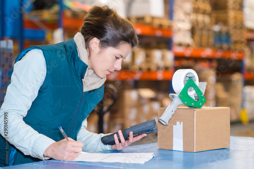 woman with carton holding scanner and filling in paperwork
