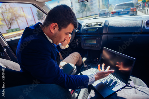 Vászonkép  Reckless businessman driving in the city during the rush hour while typing on his laptop and acting stressed out of work