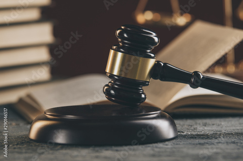 Law concept - Open law book with a wooden judges gavel on table in a courtroom or law enforcement office on black background Wallpaper Mural