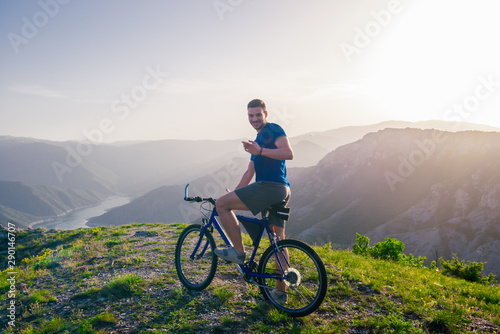 fototapeta na ścianę Adventurous Cyclist riding his mountain bike at the edge of a cliff, on rocky terrain while wearing no safety equipment.Amazing top view.