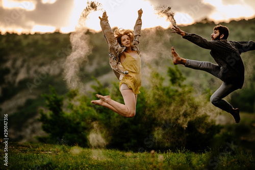 Full length of an elegant couple dancing together over sunset sky