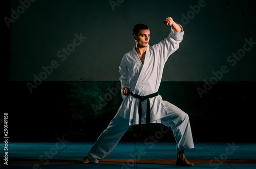 Young black belt fighter training karate in gym