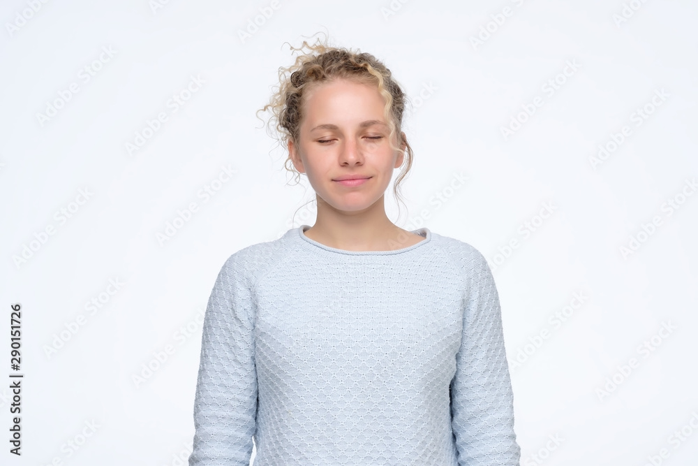 Fototapeta Calm young caucasian girl with curly hair standing with closed eyes with slight smile. Studio shot