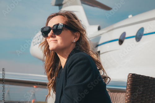 Fototapeta beautiful businesswoman is seating near the business jet airplane at a sunny day obraz