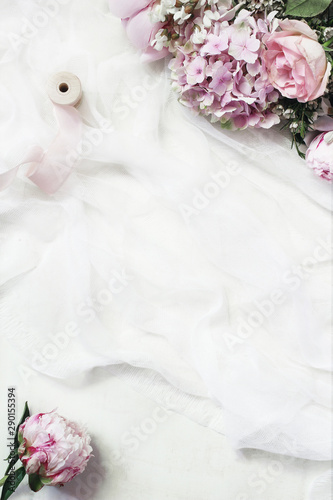 Canvas Prints Floral Feminine floral frame composition. Beautiful pink peonies, hydrangea and roses flowers on white muslin table runner background. Empty space. Wedding styled stock photo. Vertical flat lay, top view.