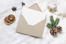 Christmas Blank Greeting Card Mock-up Scene. Festive Winter Wedding Composition. Craft Envelope, Pine Cone, Dry Orange Fruit Slices And Fir Tree Branch On White Table, Linen Background. Flat Lay, Top