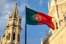 Portuguese Flag Waving In Front Of A Blue Sky And Monastery.
