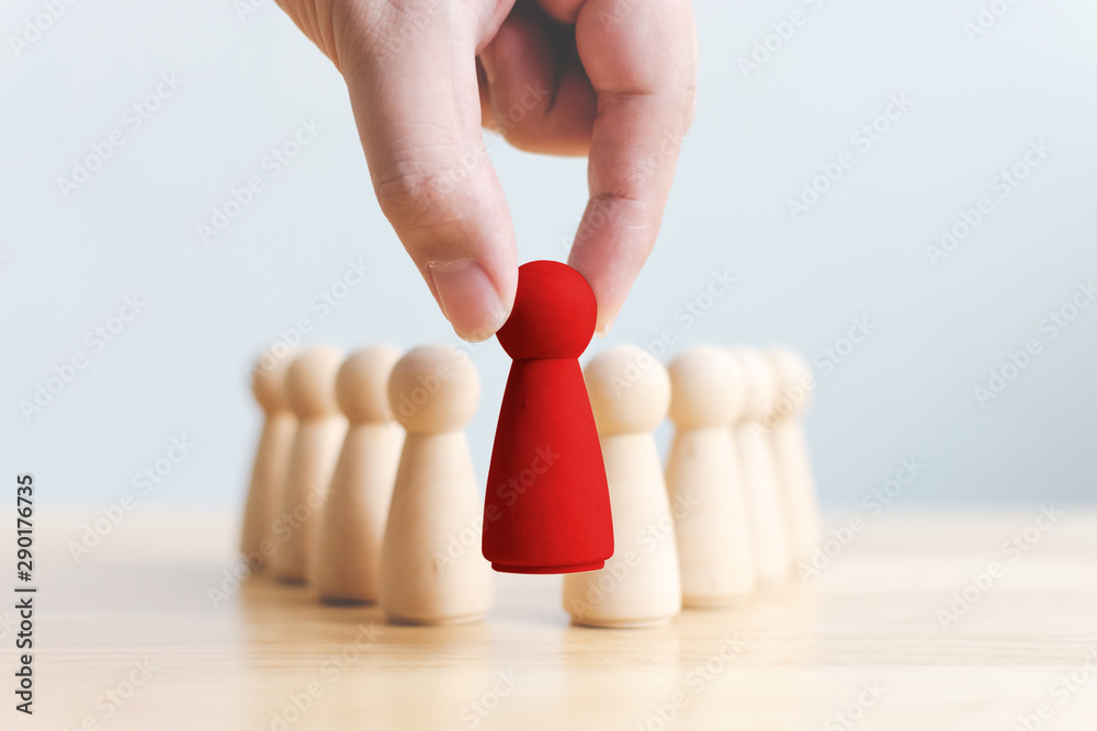 Fototapeta Human resource, Talent management, Recruitment employee, Successful business team leader concept. Hand chooses a wooden people standing out from the crowd.
